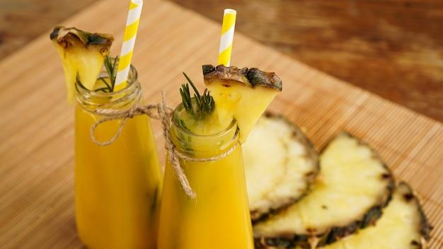 Frisch gemachter ananassaft mit eis in einer kleinen glasflasche auf holzhintergrund. hausgemachtes getränk.