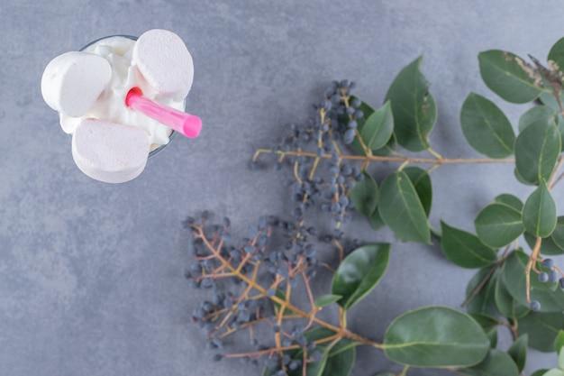 Frisch gemachter cremiger milchshake auf grauem hintergrund mit dekorativen zweigen.