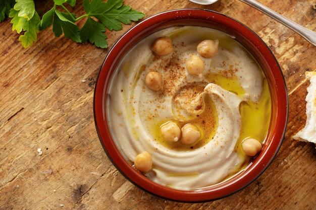 Frisch gemachter orientalischer klassischer hummus, serviert in einer schüssel auf dem tisch.