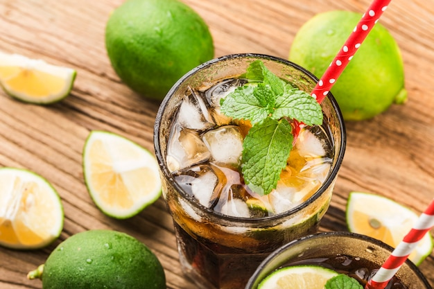 Frisch gemachtes cuba libre mit braunem rum, cola, minze und zitrone auf holzoberfläche