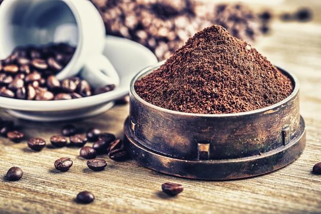 Frisch gemahlener kaffee in rustikaler mühle mit tasse und bohnen im hintergrund. alles auf holzschreibtisch gelegt