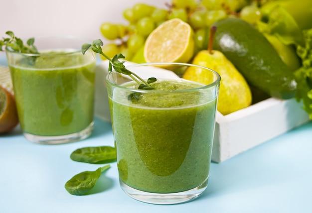 Frisch gemischter grüner smoothie in gläsern mit obst und gemüse. gesundheits- und entgiftungskonzept.