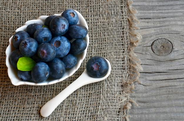 Frisch gepflückte bio-blaubeeren in einer weißen schüssel auf einem leinentuch. blaubeere. heidelbeeren. gesundes essen, veganes essen oder diätkonzept mit kopierraum. selektiver fokus.