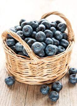 Frisch gepflückte blaubeeren auf einem alten hölzernen hintergrund. konzept für gesunde ernährung