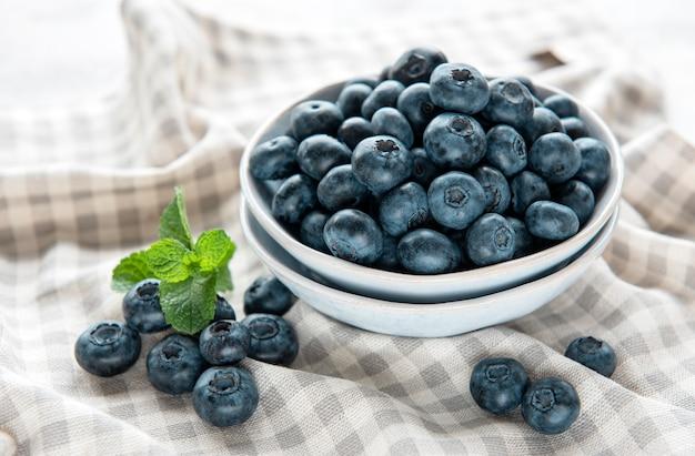 Frisch gepflückte blaubeeren auf textilhintergrund. konzept für gesunde ernährung