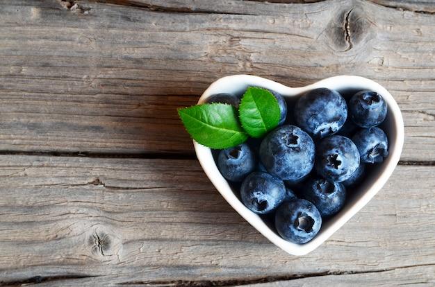 Frisch gepflückte blaubeeren in einer weißen herzförmigen schüssel. frische bio-heidelbeere. heidelbeeren. gesunde ernährung, vegane ernährung oder rohkost-konzept.