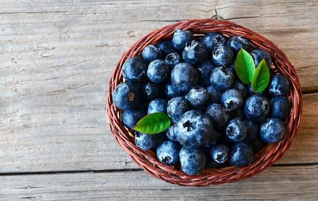 Frisch gepflückte heidelbeeren in einem korb. frische blaubeeren mit grünen blättern auf rustikaler tabelle. blaubeere. heidelbeere. konzept der gesunden ernährung, diät und ernährung.