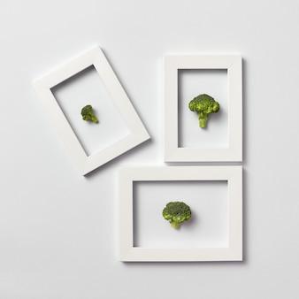 Frisch gepflückte teile des natürlichen gesunden brokkolis in einem rahmen auf einer hellgrauen wand, platz für text. draufsicht. konzept veganes essen.