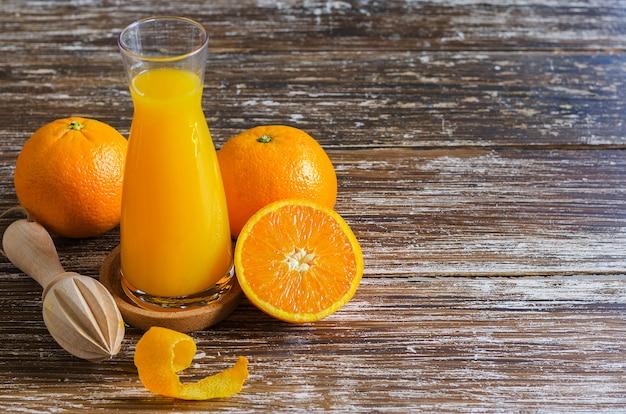 Frisch gepresster orangensaft, in zwei hälften geschnittene bio-orangenfrucht mit schalen und holzzitruspresse auf dunklem holztisch.