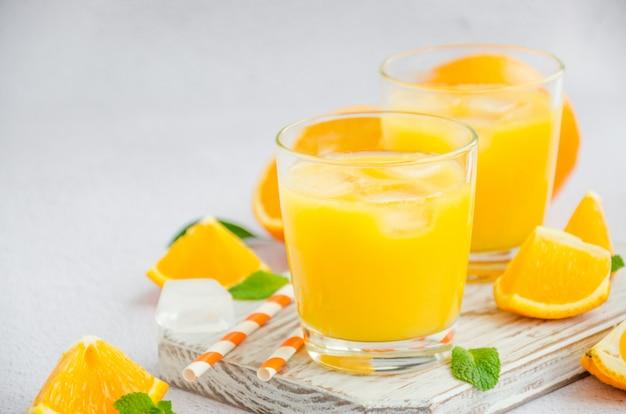 Frisch gepresster orangensaft mit eis in einem glas mit einem strohhalm auf einem holzbrett auf einer hellen oberfläche mit frischen orangen. horizontale ausrichtung, kopierraum.