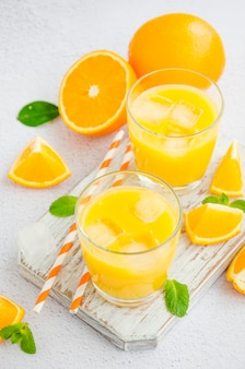 Frisch gepresster orangensaft mit eis in einem glas mit einem strohhalm auf einem holzbrett auf einer hellen oberfläche mit frischen orangen. vertikale ausrichtung, nahaufnahme.