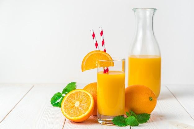 Frisch gepresster orangensaft und orangen auf einem hellen schreibtisch. seitenansicht