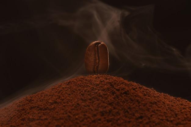 Frisch geröstete kaffeebohne steht auf einer streuung von handvoll kaffee im rauch