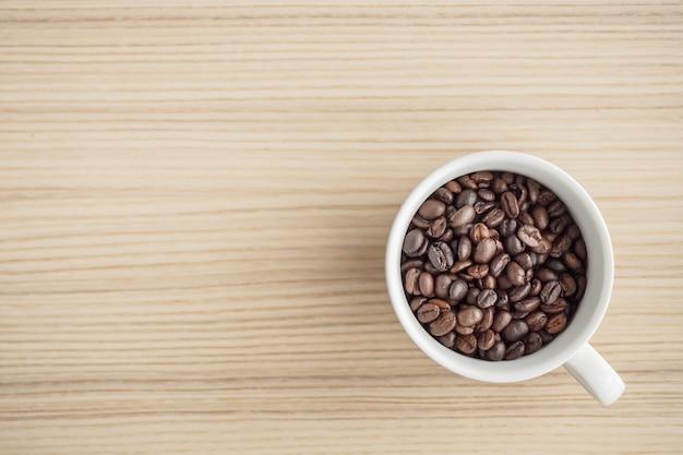 Frisch geröstete kaffeebohnen in weißer tasse auf holztisch