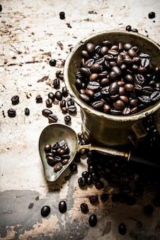 Frisch gerösteter kaffee im alten mörser. auf dem rustikalen hintergrund.