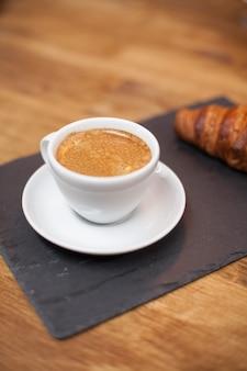 Frisch gerösteter kaffee in einer weißen tasse serviert mit leckerem croissant. kaffeearoma. leckeres croissant