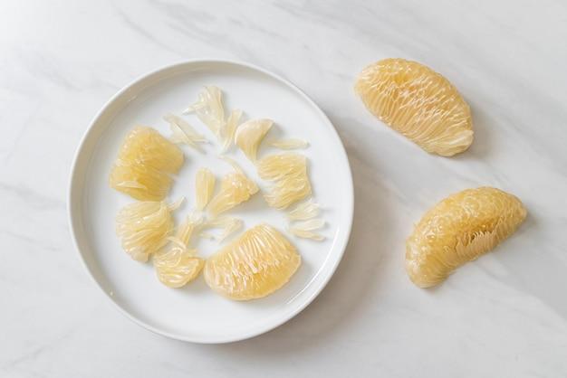 Frisch geschälte grapefruit auf weißem teller