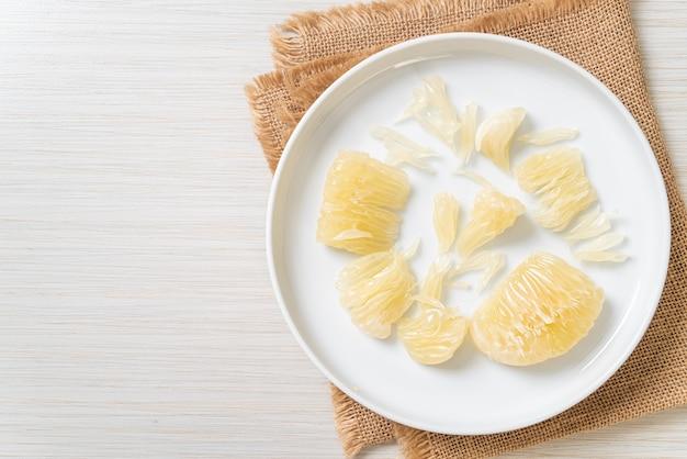 Frisch geschälte pampelmuse, grapefruit oder schellfisch auf weißem teller