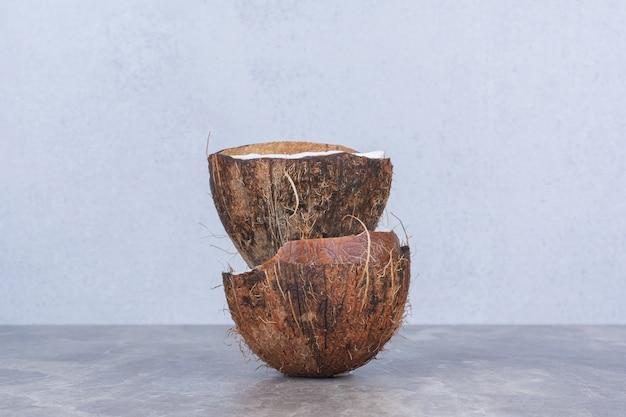 Frisch geschnittene frische kokosnüsse auf steintisch halbieren.
