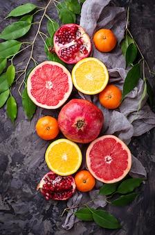 Frisch geschnittene früchte. granatapfel, orange, pampelmuse und mandarinen. selektiver fokus