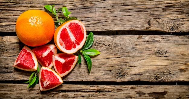 Frisch geschnittene grapefruit mit blättern auf holztisch. draufsicht