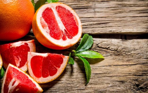Frisch geschnittene grapefruit mit blättern auf holztisch.