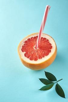Frisch geschnittene grapefruit mit strohhalm und grünen blättern auf blauem hintergrund. idee kreativ, um arbeit im rahmen einer werbe-marketing-kommunikation zu produzieren. geschäftskonzept