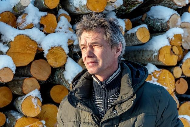 Frisch geschnittene holzscheite und brennholz von holzfällern, die während der wintersaison unter eine weiße schneedecke getaucht sind.