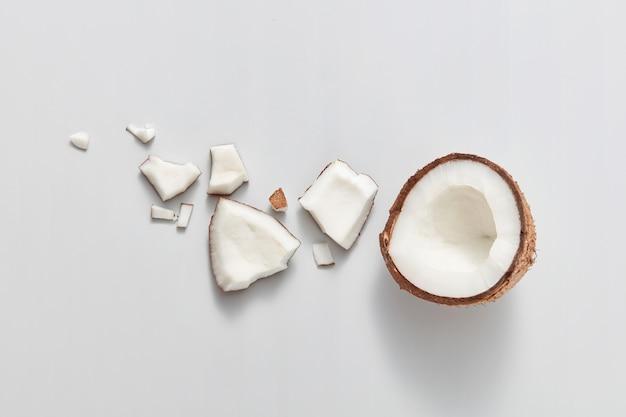 Frisch geschnittene natürliche organische stücke der natürlichen exotischen kokosnussfrucht auf einem hellgrauen hintergrund mit weichen schatten, kopienraum. vegetarisches konzept. draufsicht.