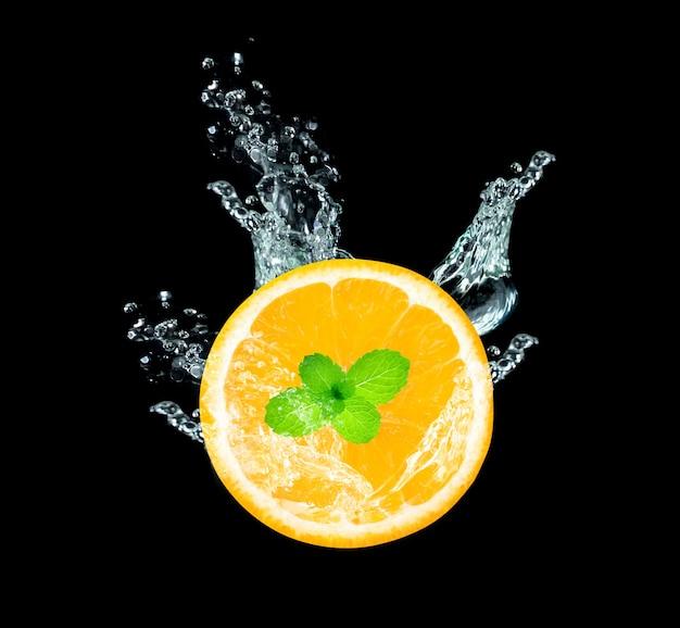 Frisch geschnittene orangenfrucht in wasserspritzer auf schwarz