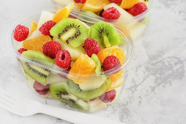 Frisch geschnittene tropische früchte im plastikbehälter