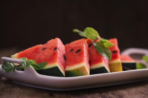 Frisch geschnittene wassermelone im weißen teller auf holztisch.