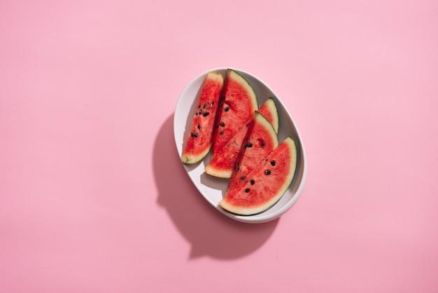 Frisch geschnittene wassermelone in weißer schale auf rosa tisch.