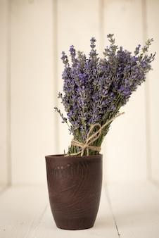 Frisch geschnittener aromatischer blumenstrauß des lavendelfeldes in einem holzglas auf weißem holz.