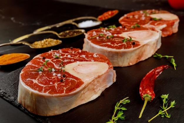 Frisch geschnittener rindfleischschenkel in knochen und gewürzen auf tafel.
