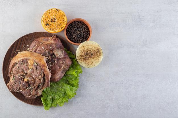 Frisch geschnittenes fleisch mit frischem gemüse auf einem steintisch.