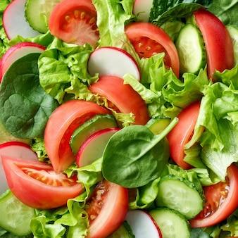 Frisch geschnittenes gemüse für die herstellung von gesundem salat, draufsicht im hintergrund