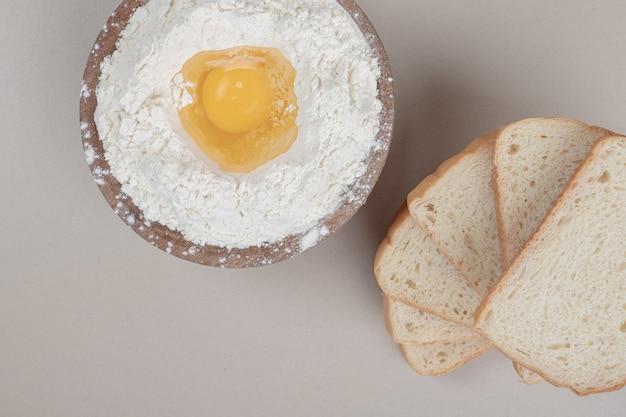 Frisch geschnittenes weißbrot mit holzschale voller mehl