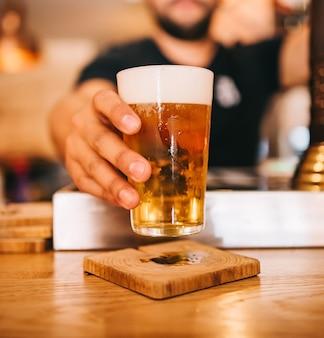 Frisch gezapftes bier. barkeeper hält ein frisch gezapftes glas bier in der hand