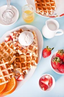 Frisch hausgemachte gebackene waffeln mit erdbeeren, honig und eis