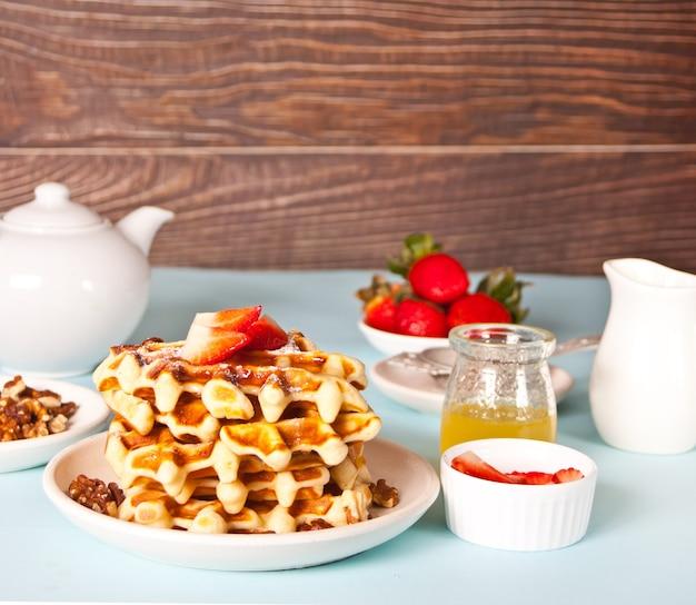 Frisch hausgemachte gebackene waffeln mit erdbeeren und honig.