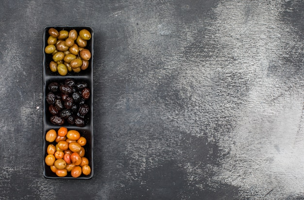 Frisch marinierte oliven in einem schwarzen teller auf dunkelgrauem grunge. draufsicht.