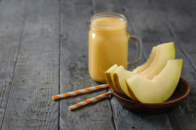 Frisch melone, orange und bananen smoothie und drei scheiben melone auf einem tisch