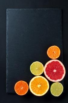 Frisch sortierte zitrusfrüchte auf dunkler oberfläche mit kopierraum