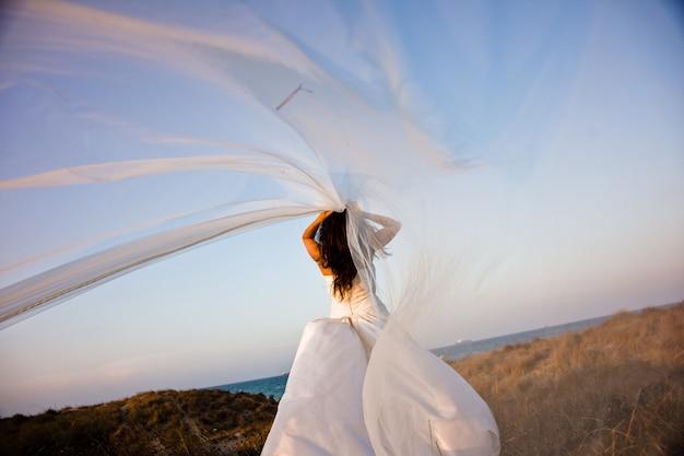 Frisch verheiratete braut mit hochzeitskleid auf einem hügel, die ihren schleier im wind flattern lässt