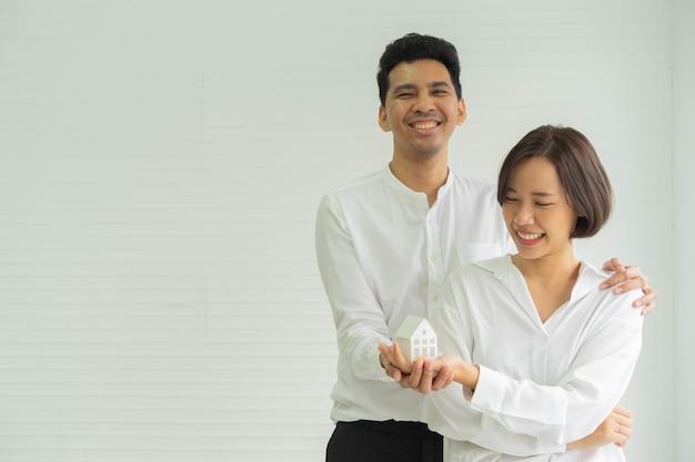 Frisch verheiratetes paar, das zu hause steht und das modell des hauses zusammenhält