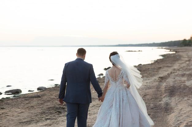 Frisch verheiratetes paar, das zusammen am strand weggeht