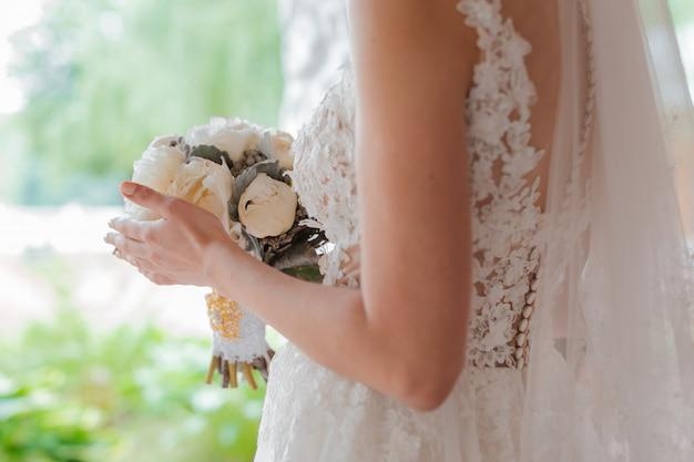 Frisch verheiratetes paar. hochzeitstag. blumenstrauß der braut in den händen, die umarmung des bräutigams.