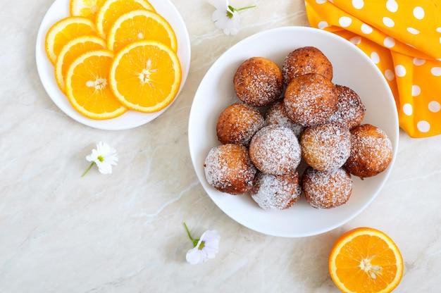 Frisch zubereitete donuts mit puderzucker in einer weißen schüssel. quarkbällchen pommes. dessert aus dem hüttenkäse