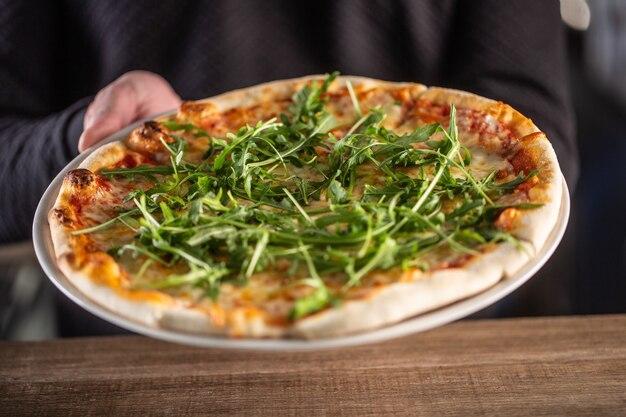 Frisch zubereitete italienische pizza mit tomatensauce und rucola.